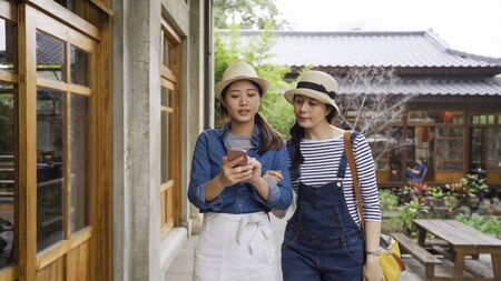 two attractive asian female friends walking outdoors looking at cellphone discussing route of tour trip in kyoto japan.