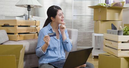 Photo pour happy young asian chinese woman pensive holding credit card and smiling thinking while using laptop computer in new home sitting on floor surrounding by cardboards boxes in living room joyful move. - image libre de droit