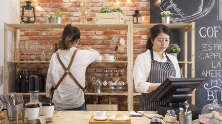 Foto de elegant young lady waitress hands touching tablet screen checking order. two girls staff working in modern cafe bar. - Imagen libre de derechos