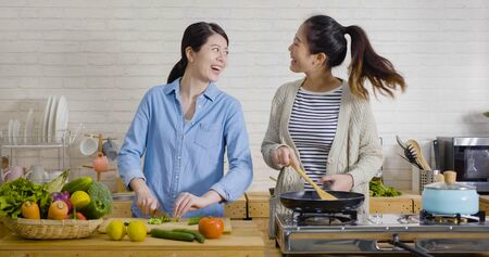 Foto de Young female friends in kitchen cooking together vegetarian meal. Preparing fruit salad healthy food in morning kitchen. happy asian women singing dancing and having fun while cutting and frying - Imagen libre de derechos