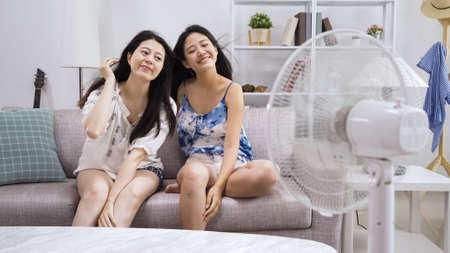 Photo pour elegant cute ladies friends sitting close in sofa in comfort living room at home. beautiful female in shorts enjoy electric fan wind blowing hair smiling close eyes. girls feeling air cooler in house - image libre de droit