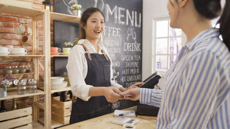 Photo pour businesswoman customer at coffee shop pays smiling waitress with debit card. young girl barista using tablet while client doing payment on recharge card in cafe counter. happy small business owner. - image libre de droit