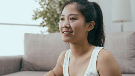 closeup attractive asian female in ponytail smiling contentedly. positive and confident image korean beautiful girl looking into distance and beaming with happiness.