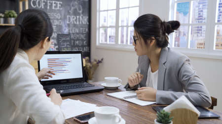 Serious businessman pointing at laptop computer monitor discussing corporate software with colleague in modern cafeteria. executive female team partners working together use notebook in coffee shop