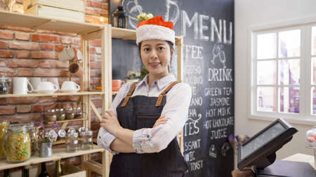 Photo pour Portrait of confident young woman worker wearing apron and red santa hat standing behind cafe counter looking at camera. - image libre de droit