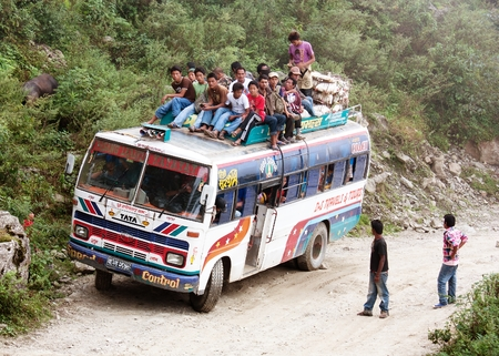 LANGTANG AREA, NEPAL, 20th OCTOBER 2010 - people traveling on top of autobus brand TATA in Nepalese Himalayan mountain road