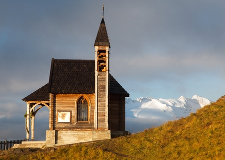 Morning view of small wooden church or chapel on the mountain top Col di Lana and Mount Marmolada, Alps Dolomites mountains, Italy