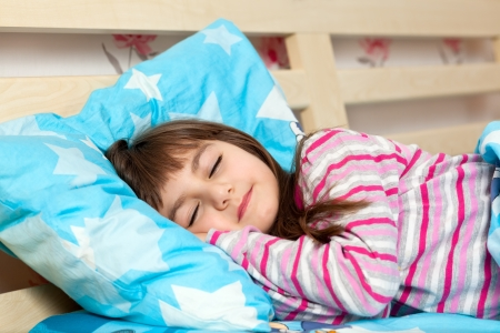 beautiful little girl in pajamas sleep in bed under a blue blanket
