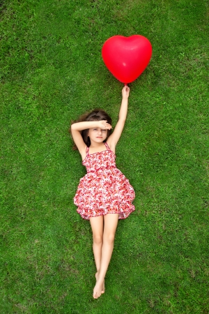 beautiful girl in color dress lying on the grass and holding a red ball in the form of heartの写真素材
