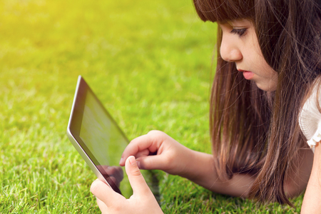 Photo pour little girl lying on green grass and touches the screen a tablet - image libre de droit