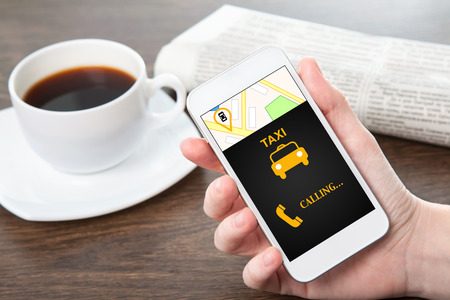 businesswoman hand holding a phone with interface taxi against the background of the table in the office