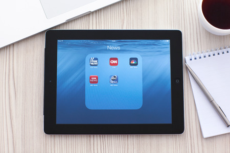 Simferopol, Russia - September 13, 2014: iPad lies on a table with popular news applications on the screen. iPad is created and developed by the Apple inc.