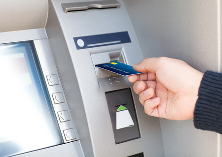 Photo pour man hand puts credit card into ATM - image libre de droit