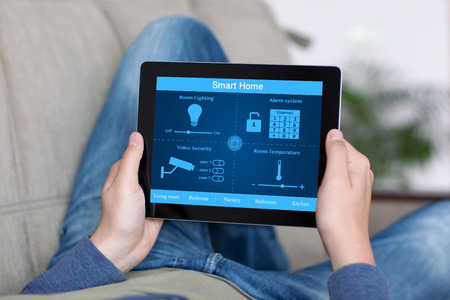 man lying on a sofa and holding a tablet with program smart home on the screen