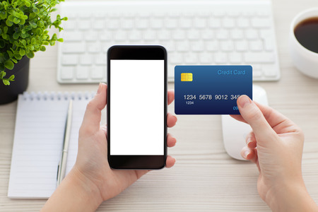 female hands holding phone with isolated screen and a credit card over the desk in the office