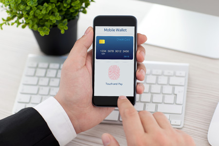 Foto für businessman sitting at the desk in office and holding phone with app mobile wallet and fingerprint for online shopping - Lizenzfreies Bild