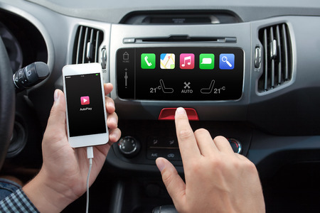 man connecting phone with auto play to the car media system