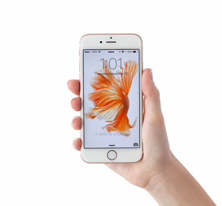 Photo pour Alushta, Russia - November 12, 2015: Woman unlock iPhone6S Rose Gold in the hand on the white background. iPhone 6S Rose Gold was created and developed by the Apple inc. - image libre de droit