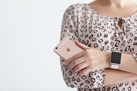 Photo pour Alushta, Russia - October 22, 2015: Woman with Apple Watch in the hand holding iPhone 6 S Rose Gold. iPhone 6S and Watch was created and developed by the Apple inc. - image libre de droit