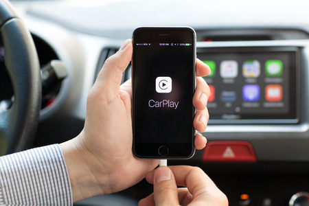Photo pour Alushta, Russia - May 31, 2016: Man hands holding iPhone 6 with Car Play in the screen on the background multimedia system auto. iPhone and Car Play was created and developed by the Apple inc. - image libre de droit