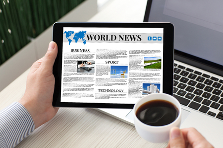 Photo for man holding tablet computer with world news on screen and coffee near notebook - Royalty Free Image