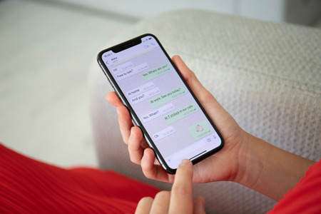 Photo pour Alushta, Russia - September 27, 2018: Woman holding iPhone X with social networking service WhatsApp on the screen. iPhone 10 was created and developed by the Apple inc. - image libre de droit