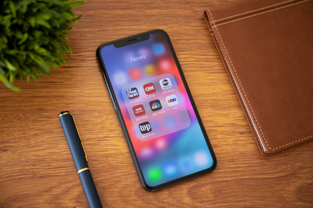 Alushta, Russia - October 13, 2018: iPhone X with popular news applications on the screen and background wooden desk. iPhone ten is created and developed by the Apple inc.
