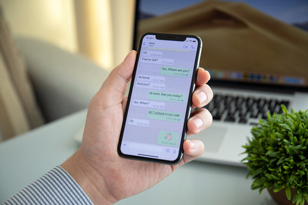 Photo pour Alushta, Russia - October 9, 2018: Man holding iPhone X with social networking service WhatsApp on the screen. iPhone 10 was created and developed by the Apple inc. - image libre de droit