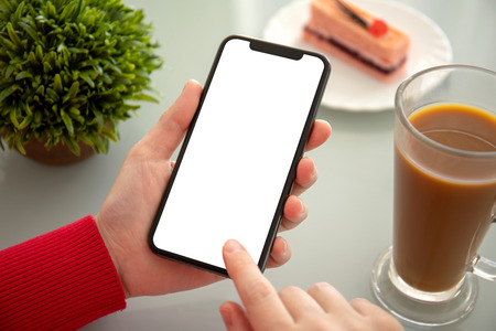 Photo pour female hands holding phone with isolated screen above the table in a cafe - image libre de droit