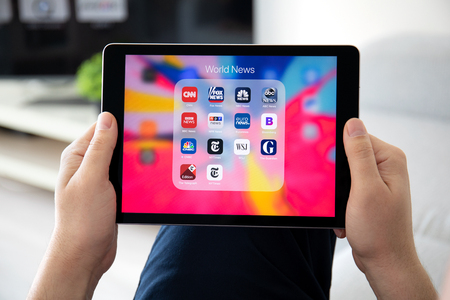 Anapa, Russia - March 26, 2019: Man hand holding iPad Pro with popular news applications on the screen. iPad Pro is created and developed by the Apple inc.