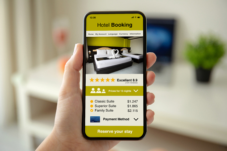 Photo pour female hands holding phone with app hotel booking on the screen in the house in room - image libre de droit