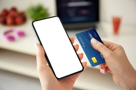 Photo pour female hands holding phone with isolated screen and credit card on the background room - image libre de droit