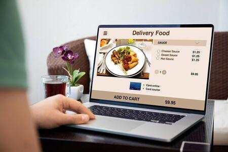 Foto de male hands on laptop keyboard with food delivery application on the screen  - Imagen libre de derechos