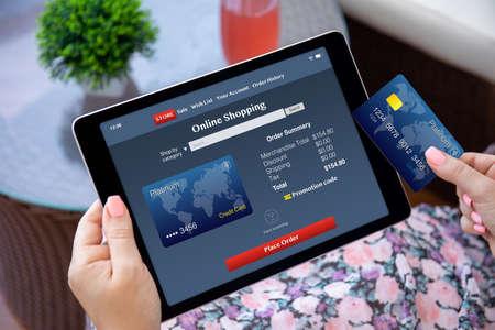Foto de female hands holding computer tablet with app online shopping on screen and plastic credit card - Imagen libre de derechos