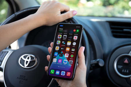Photo pour Alanya, Turkey - September 23, 2020: Woman hand holding iPhone 11 with Widgets call phone on the screen IOS 14 in the Toyota car. - image libre de droit