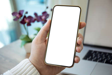 Photo pour Man hands holding golden phone with isolated screen over white table in office - image libre de droit