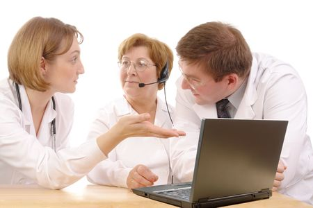Two young interns consulting medical problem with senior doctor wearing headset sitting behind desk with laptop over white