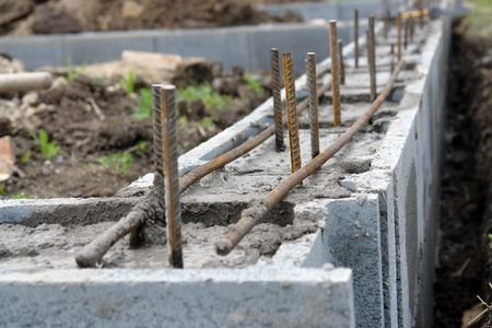 Closeup of house foundation made from concrete shuttering blocks filled with mortar and reinforcement bars