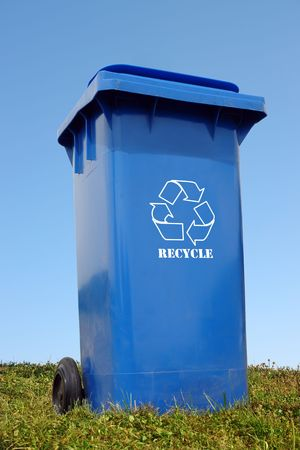 Blue plastic disposal bin with white recycle symbol in the grass over blue sky