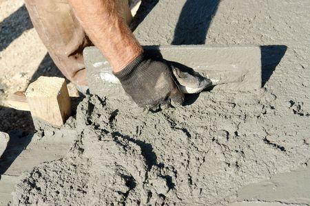 Photo pour Closeup of mason's hand spreading concrete mix with trowel in foundation shuttering - image libre de droit
