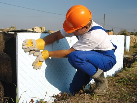 Construction worker fitting styrofoam thermal insulation panels to house foundation walls