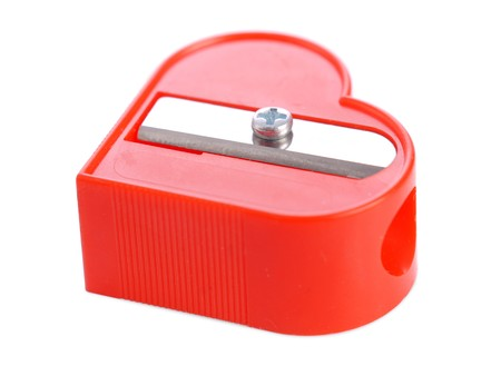 Red plastic heart-shaped pencil sharpener over white background