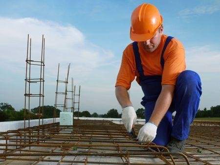 Bar bender fixing steel reinforcement for house concrete floor slab