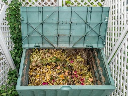 Green plastic compost bin full of organic and domestic food scraps