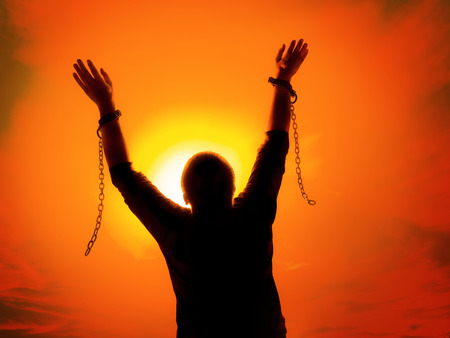 Photo pour Silhouette of man agains the sunset ssky raising up his hands as he becomes free from chains and shackles - image libre de droit