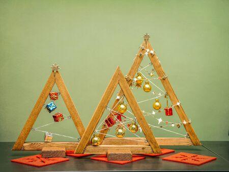 Photo pour Wooden christmas tree shape decorations against green wall - image libre de droit