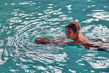 Photo pour Woman learning to swim, practicing in swimming pool using a board. Candid people, real moments, authentic situations - image libre de droit
