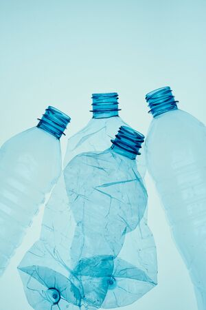 Photo pour Empty plastic squashed bottles over blue background. Collecting plastic waste to recycling. Concept of plastic pollution and too many plastic waste. Copy space for text - image libre de droit