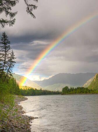 Photo pour rainbow above river in mountains - image libre de droit