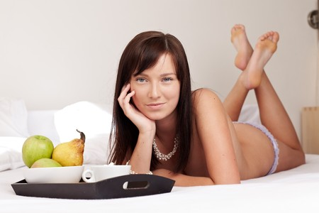 Young beautiful woman having breakfast lying on white bed の写真素材